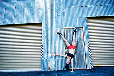 Caucasian woman doing one-handed handstand outdoors - p555m1304121 by Peathegee Inc