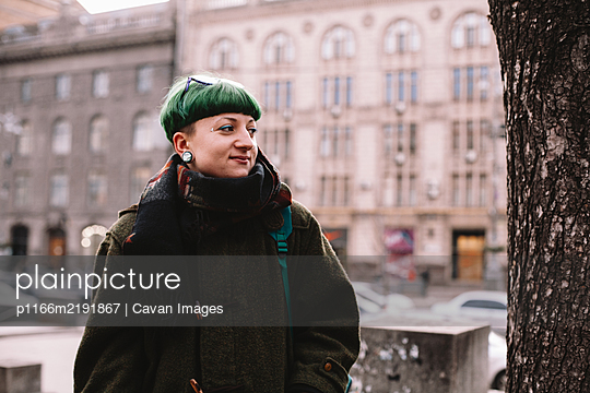 Portrait of happy hipster woman standing on street in city - p1166m2191867 by Cavan Images