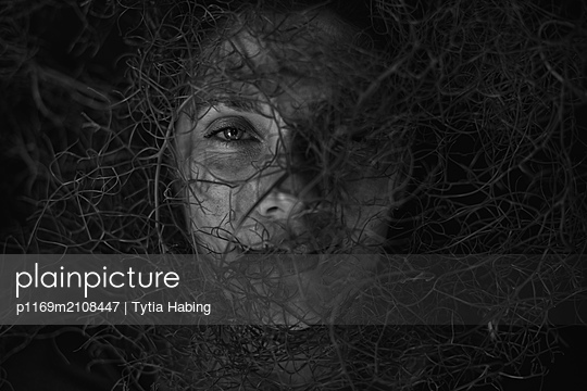 woman's face behind vines - p1169m2108447 by Tytia Habing