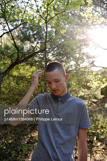Jugendlicher blickt nach unten am Waldrand - p1468m1584966 von Philippe Leroux