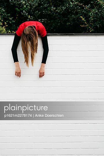 Girl hanging down a wall - p1621m2278174 by Anke Doerschlen