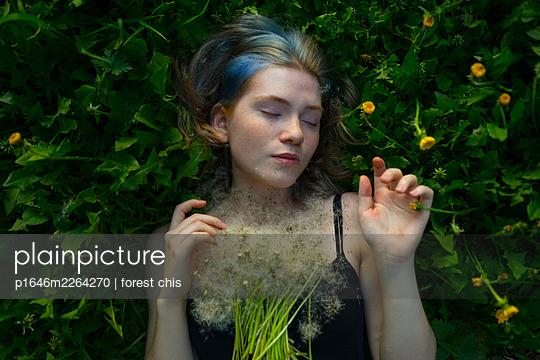 Junge Frau liegt mit geschlossenen Augen auf einer Wiese - p1646m2264270 von Slava Chistyakov