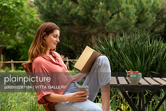 Woman with coffee mug reading book while sitting on chair in garden - p300m2287184 by VITTA GALLERY