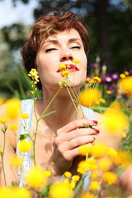 Woman enjoying flowers - p045m831259 by Jasmin Sander