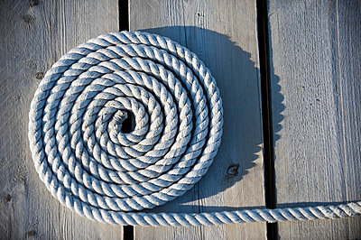 Close-up of coiled rope on wood paneled surface - p1025m780271f by Björn Andrén