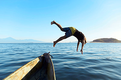 Man jumping from boat into sea - p1166m2157340 by Cavan Images
