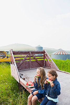 Girls eating watermelon on farm - p1192m1014238f by Hero Images