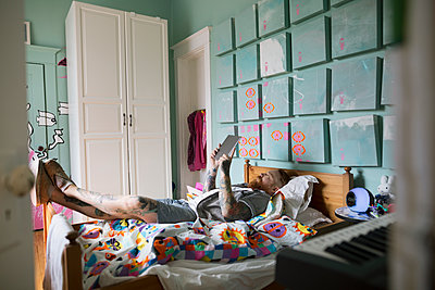 Father laying on bed and reading digital tablet - p1192m1158179 by Hero Images
