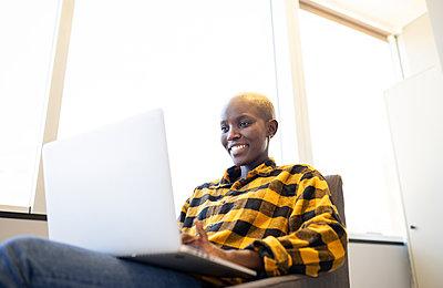 Smiling woman wearing checkered shirt using laptop at home - p300m2282180 by Jose Carlos Ichiro