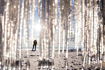 Silhouette of person on beach. icicles on foreground - p312m1114105f by Henrik Trygg