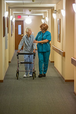Older Caucasian woman walking with nurse in nursing home - p555m1420932 by Steve Smith