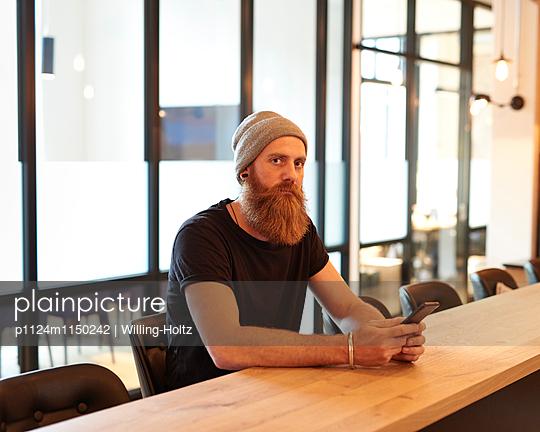 Mann sitzt an einem Konferenztisch mit Smartphone - p1124m1150242 von Willing-Holtz