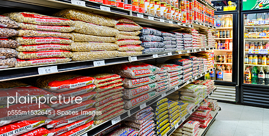 Bags of food on shelves of grocery store - p555m1532645 by Spaces Images