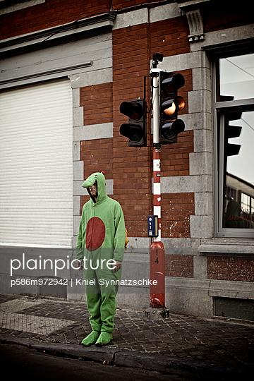 Ein Mann in einem grünen Kostüm steht an einer Ampel - p586m972942 von Kniel Synnatzschke