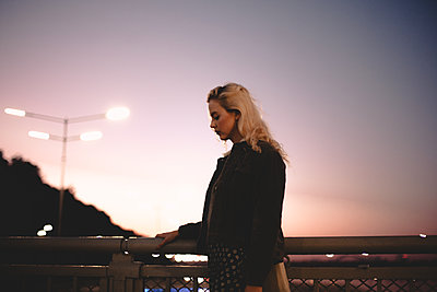 Young woman standing on bridge against sky at sunset - p1166m2153565 by Cavan Images