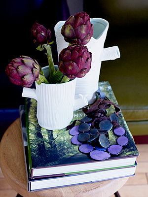 Purple artichoke flowers in vase with necklace and books. - p349m2167822 by Polly Wreford