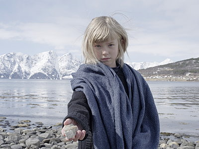 Blonde girl showing pebble stone - p945m1444657 by aurelia frey