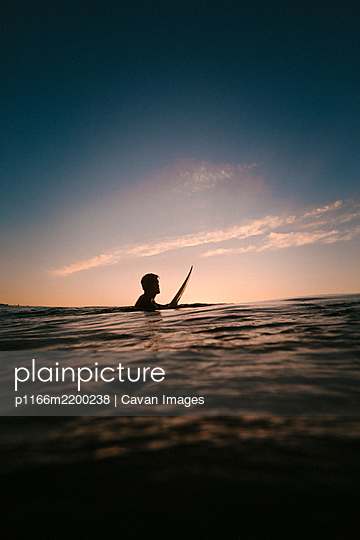 surfer under the sunset on a beach in Spain - p1166m2200238 by Cavan Images