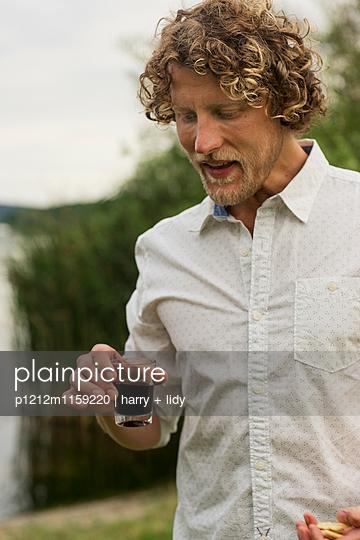 Mann mit einem Glas Wein am See - p1212m1159220 von harry + lidy