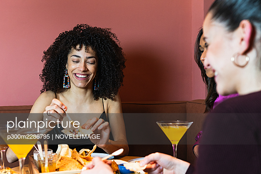 Barcelona, Spain. Smiling female friends dining in restaurant. 20-30 years, birthday, celebration, restaurant, multicultural, three people, party, friendship, dining table, multiracial group, togetherness, fun, meals, drink, people, smartphone, happy - p300m2286795 von NOVELLIMAGE