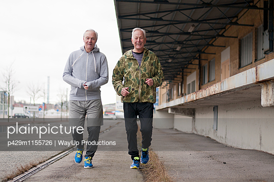 Senior friends wearing sports clothes jogging side by side - p429m1155726 by WayUp Productions