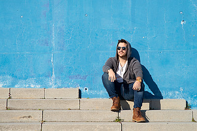Portrait of stylish man sitting on stairs leaning on a blue wall - p1166m2131185 by Cavan Images