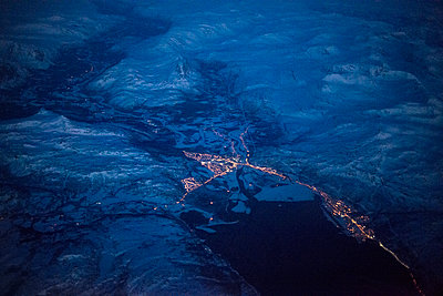 Snow-covered mountains and city lights shot by night, from above - p1216m2187286 by Céleste Manet