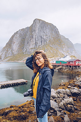 Norway, Lofoten, Hamnoy, portrait of young woman with camera - p300m2059363 by CSSHOT