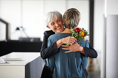 Happy senior businesswoman with bunch of flowers hugging colleague in office - p300m2181090 by Rainer Berg