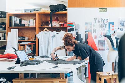 Fashion designer cutting fabric from dressmaker's pattern - p429m2058497 by Eugenio Marongiu