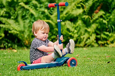 Toddler playing with push scooter in park - p429m2164684 by GS Visuals