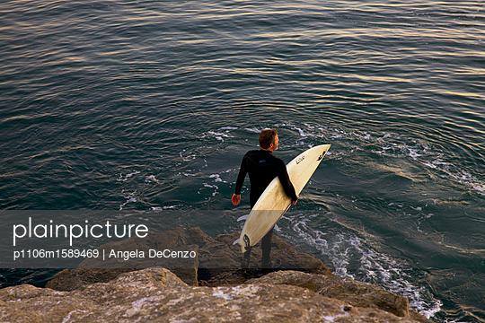 Mann mit Surfbrett an der Küste - p1106m1589469 von Angela DeCenzo