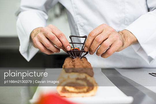 Pastry chef decorating cake with chocolate figures - p1166m2130379 by Cavan Images