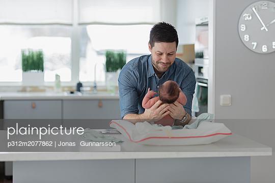 Man changing babys diaper - p312m2077862 by Jonas  Gunnarsson
