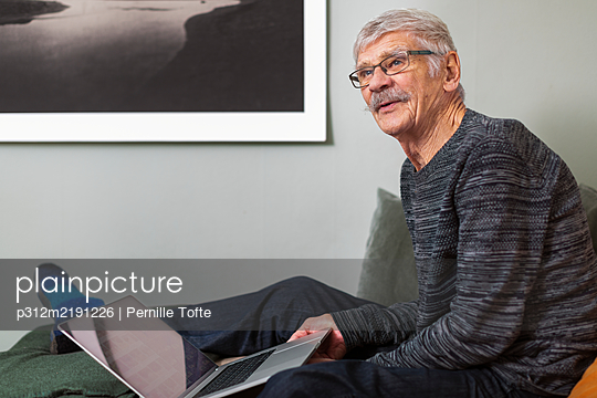 Senior man with laptop on sofa - p312m2191226 by Pernille Tofte