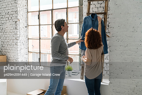 Couple moving into industrial style apartment, looking at denim shirt - p429m2091449 by Garage Island Crew