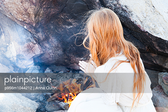 Girl warming her hands on fire - p956m1044212 by Anna Quinn