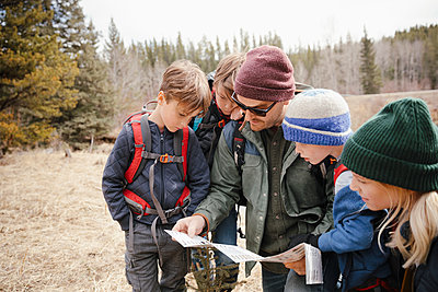 Family with trail map hiking in woods - p1192m2094167 by Hero Images