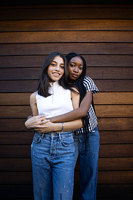 Two teenage girls embrace each other - p1640m2259891 by Holly & John