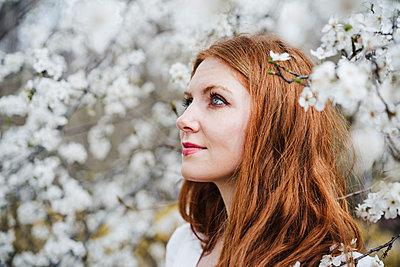 Redhead woman amidst white almond tree looking away - p300m2274561 by Eva Blanco