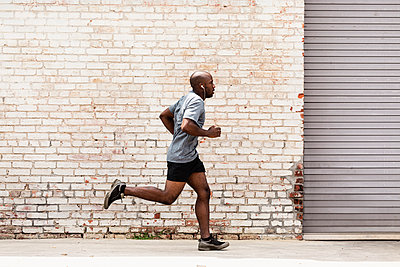 Black man running on city sidewalk - p555m1420904 by Roberto Westbrook