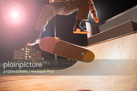 Young man skateboarding on ramp at skate park - p1023m2200952 by Himalayan Pics