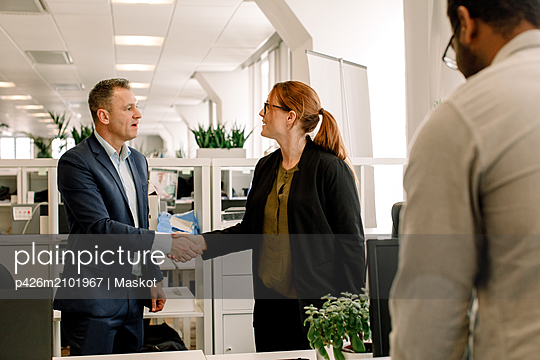 Businesswoman shaking hand with sales manager in office - p426m2101967 by Maskot