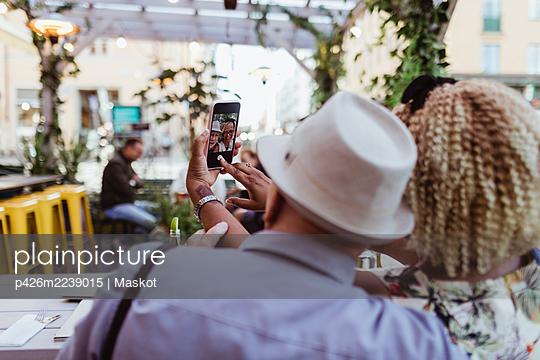 Rear view of senior couple taking selfie in sidewalk cafe - p426m2239015 by Maskot