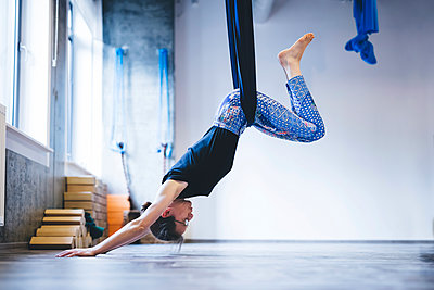Woman hanging on hammock while practicing anti-gravity yoga in gym - p1166m1576472 by Cavan Images