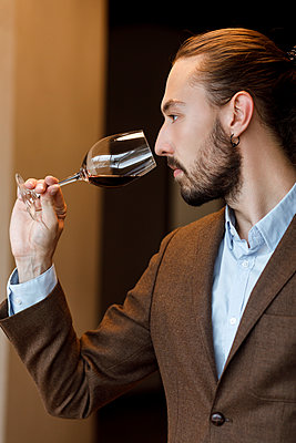 Young man smelling wine in glass at tasting - p1427m2110158 by Mykhailo Lukashuk