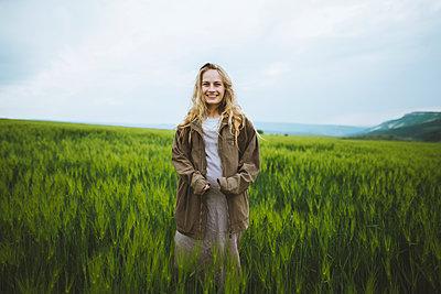Smiling woman wearing jacket in field in Crimea, Ukraine - p1427m2163664 by Oleksii Karamanov
