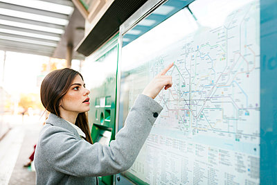 Spain, Barcelona, young woman looking at map at station - p300m1587822 by Valentina Barreto
