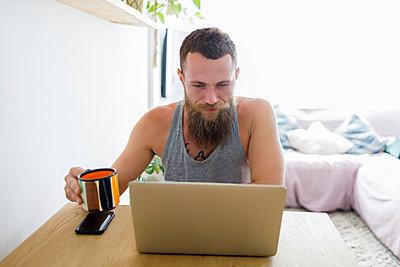 Bearded man using laptop while holding coffee cup at home - p300m2240879 by Ignacio Ferrándiz Roig