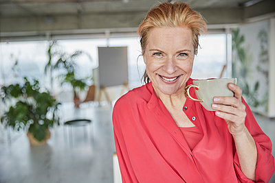 Beautiful mature woman with coffee cup at home - p300m2266082 by Jo Kirchherr